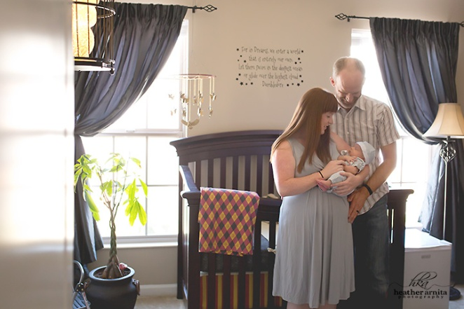 columbus ohio newborn photography mom and dad with baby in nursery in front of crib