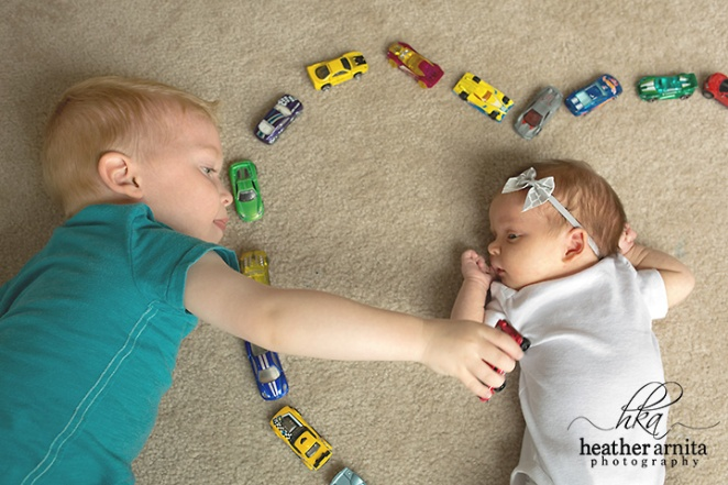 newborn lifetyle session in columbus ohio big brother playing cars with baby