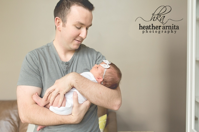 newborn lifetyle session in columbus ohio dad smiling down on baby in his arms