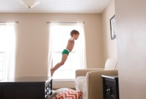 lifestyle photography boy jumping onto couch